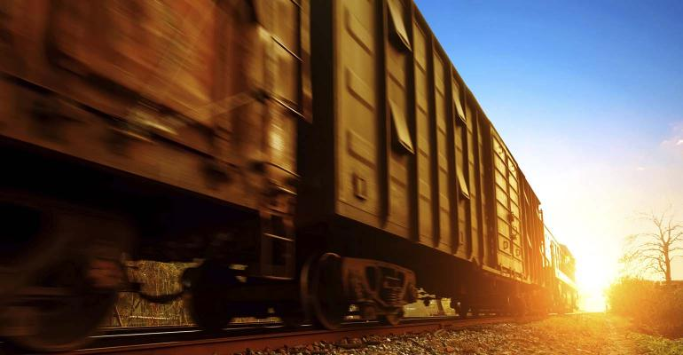 Freight train rolling along tracks.