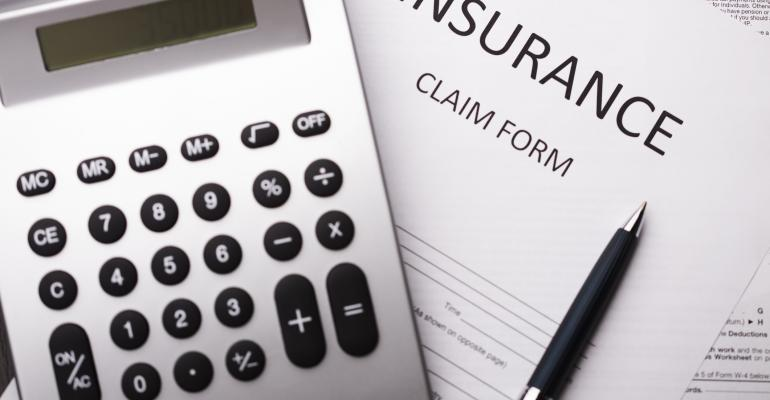 Insurance claim form with calculator and pen
