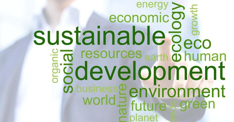 Businessman touching green tag cloud about sustainable development with office buildings in background