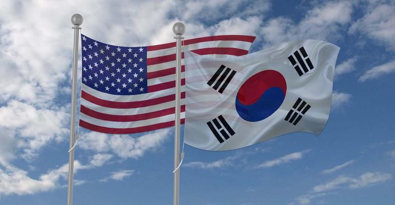 U.S. and South Korean flags waving with blue sky background.