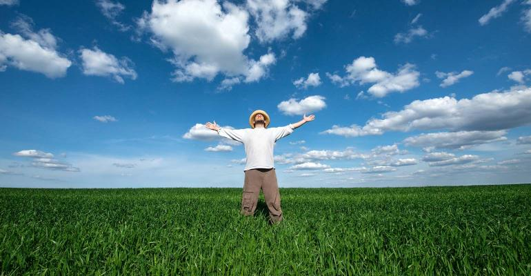 young man in wheat field reaching for the blue sky