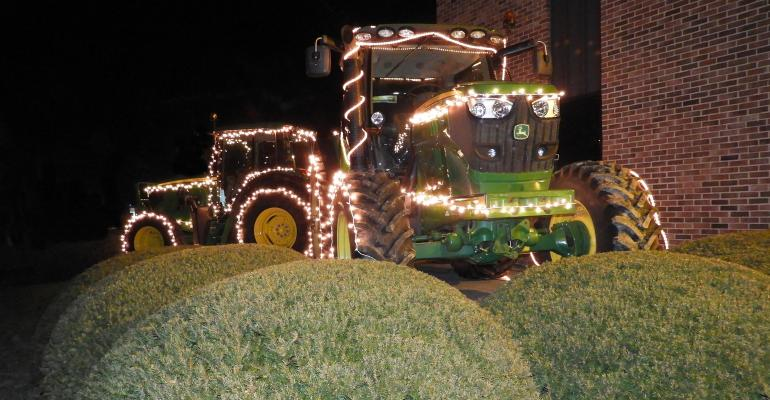 Two John Deere Tractors on display lit up with Christmas lights