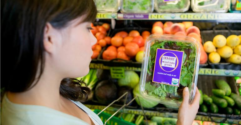 girl looking at a package of organic lettuce in grocery store