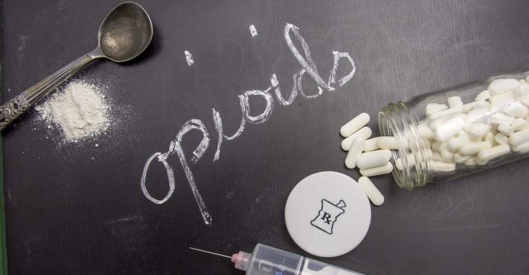 Opioids written in chalk on blackboard with crushed powder, spoon, syring and prescription vial.