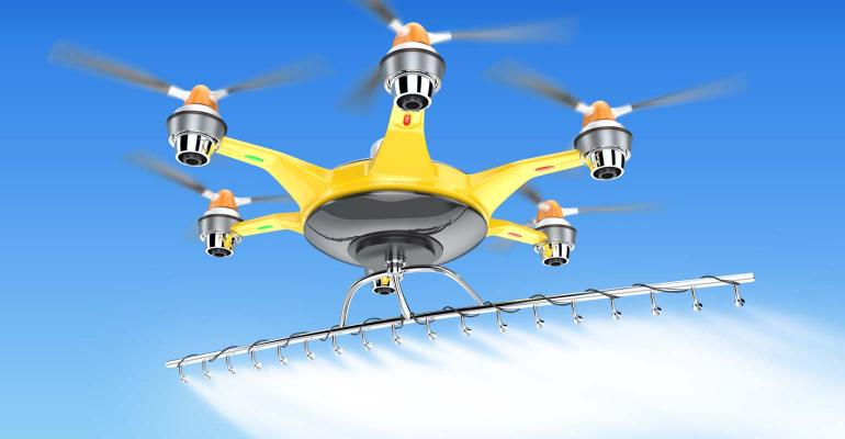 Yellow drone flying in blue sky.