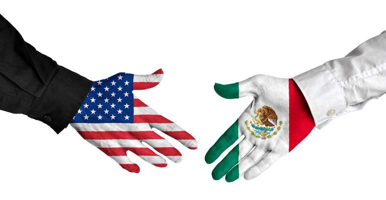 Hand in U.S. flag and hand in Mexican flag reaching out for handshake.