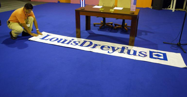 Hector Rainey from Louis Dreyfus rolls a banner out in front of the desk where they will sign an agreement for trade with the Cuban government September 27, 2002 in Havana, Cuba.