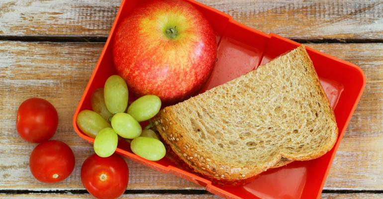 Lunchbox filled with grapes, apple, half sandwich