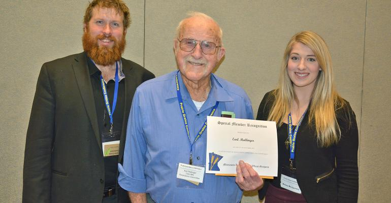 Earl Mallinger recognized at the Prairie Grains Conference, grandchildren, Evan and Melissa Montgomery behind