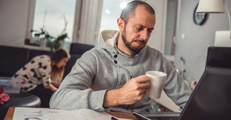 Man drinking coffee and working on laptop at home