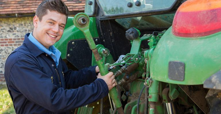 Mechanic repairing tractor. Mechanic smiling at camera. Using wrench on back of tractor.