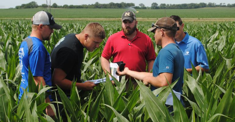 Producers inspect field maps on a smartphone during a Bazile Groundwater Management Area tour near Royal, Neb. The management area's goal is to reduce nitrates in local groundwater.