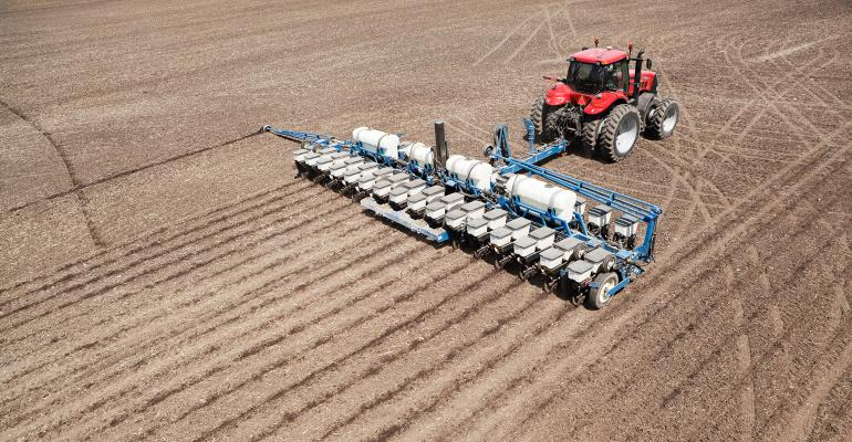 A low aerial view of a tractor planting a cornfield.
