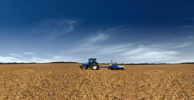 Blue tractor and planter planting soybeans