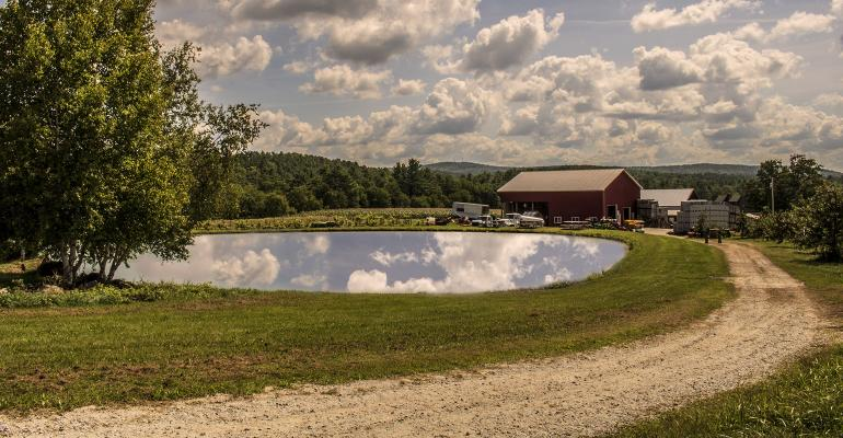 The crystal clear pond at the Apple Hill Farm in Concord, NH, reflects the sky above.