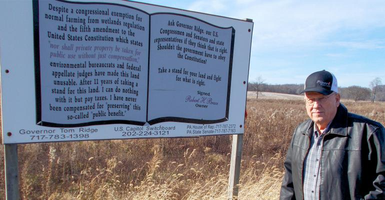 Bob Brace, Erie County, Pa, stands by a sign that explains his battle with the federal government over his farm's Wetlands Restoration Plan.