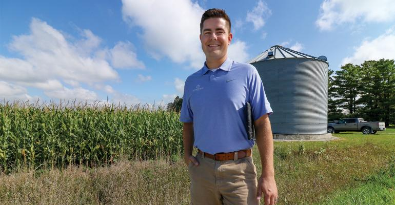 Farmer standing in field with cover crops, corn and bins in background.