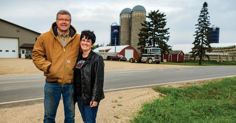 Man and woman standing outside a farm.