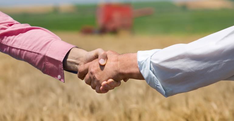 People shaking hands in farm field.