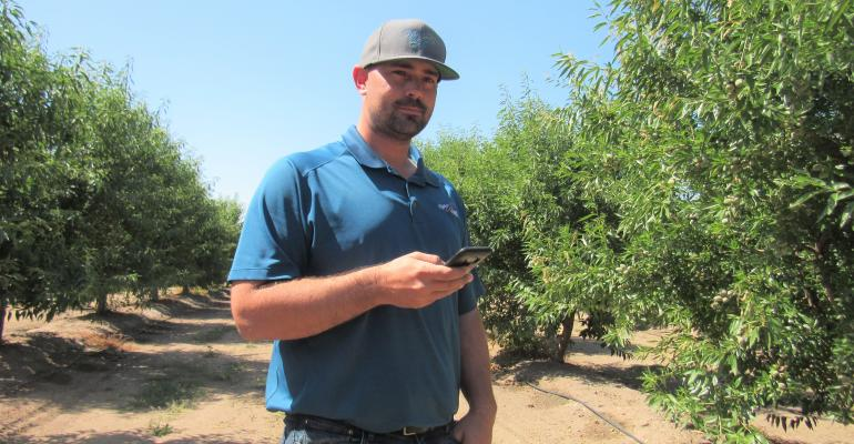 Grower with hand-held device in orchard