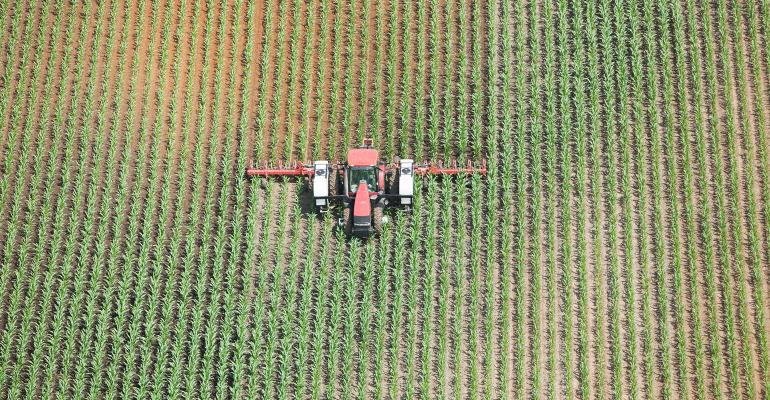Aerial view of a tractor towing an applicator is spraying liquid nitrogen fertilizer on a late Spring corn field. The left corn and behind the spreader is wet with darker soil. Shot from the open window of a small plane.