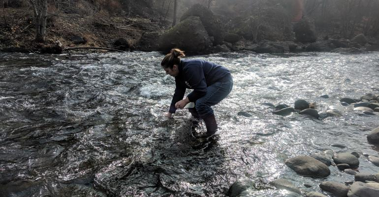 Tracy Schohr tests water in a creek