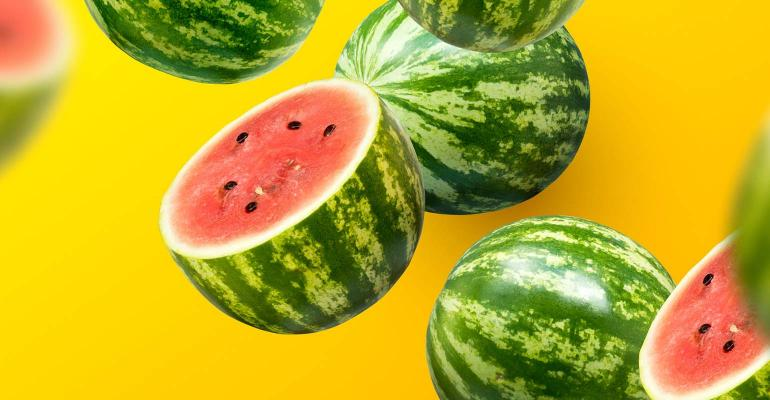 Watermelons sliced and whole on a yellow summer background.