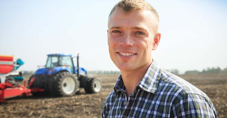 Young attractive man near a tractor.
