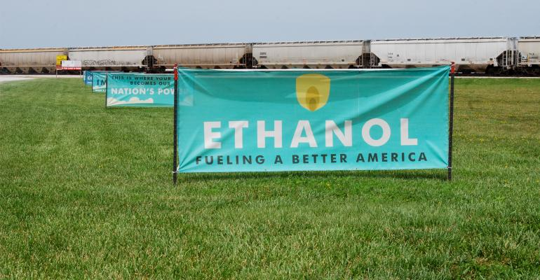 Signage promoting ethanol appears in field with grain-hauling railway cars in the distance