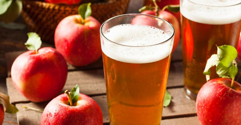 Two pints of craft cider surrounded by apples
