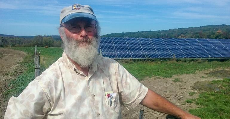 Kim Shaklee shown with 29-kW solar array at his dairy