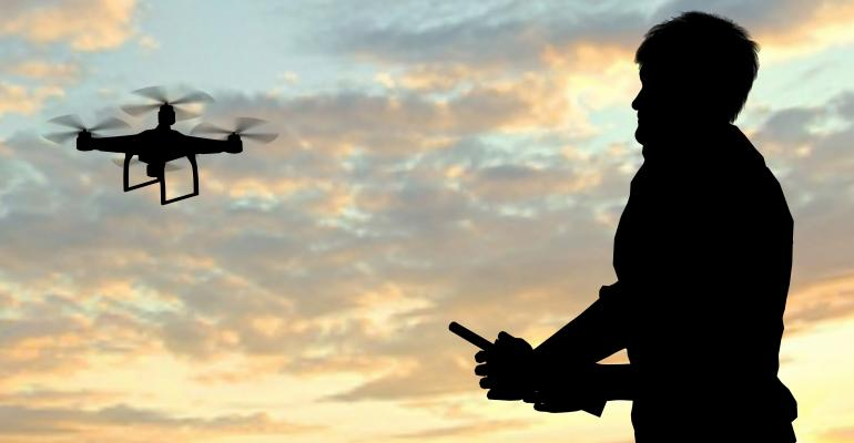 Man operating a flying drone quadrocopter at sunset - Thinkstock