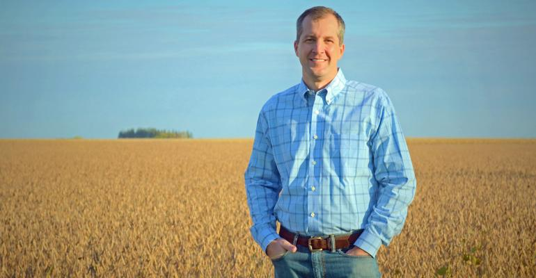Mike Naig in front of soybean field