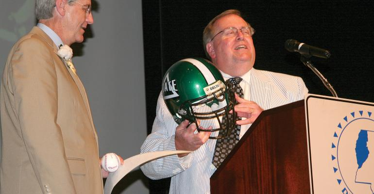 DELTA STATE UNIVERSITY President John Hilpert right presents a DSU football helmet to Gov Phil Bryant at the Delta Council annual meeting Hilford presented the helmet a baseball signed by Delta State legend Boo Ferris and a Delta State pennant after noting that Bryant did not have any Delta State memorabilia in his office in the Governorrsquos Mansion in Jackson
