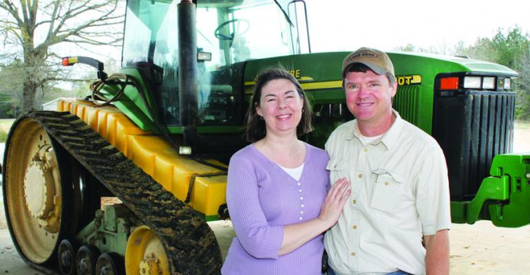KEITH MORTON and wife Beth with the tracked tractor thatrsquos a part of Keithrsquos program of utilizing precision farming technology and notill to reduce compaction and maintain beds in the same place year after year