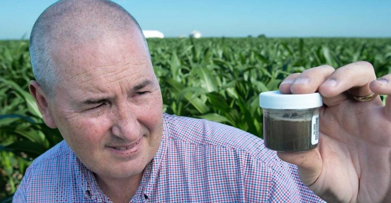 Farm manager Jim Goss holds a plastic jar containing a special ionexchange resin mixed with soil and water which can detect deficiencies of more than a dozen nutrients before plants show symptoms
