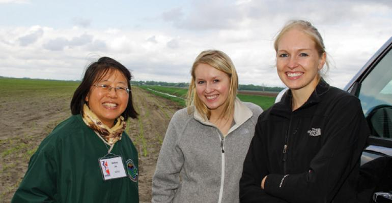 Xinhua Jia left an agricultural engineer with North Dakota State University Extension is testing combined subsurface drainage and irrigation on this 108acre cornfield with Fairmount ND farmers Alicia Miller Holubok center and Amanda Miller Fisher