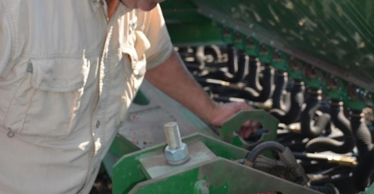 MIKE FALLON CHECKS his planter as he puts in his 2015 wheat crop