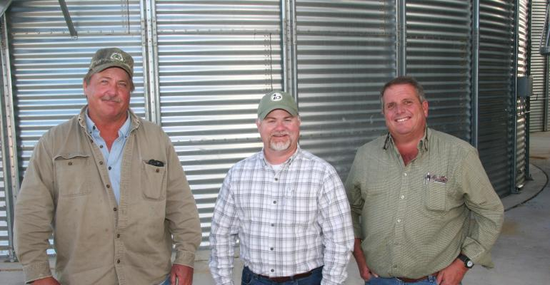 MIKE ROHWER left owner Spirit Farms Shane Bray center territory manager International Farming Corp LLC and Malcolm McClanahan producer visit in front of one of the grain bins IFC installed between their farming operations near Lake Cormorant Miss
