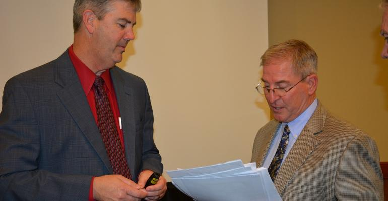 JOE OUTLAW Extension economist and codirector of the Agricultural and Food Policy Center in College Station reviews some paperwork with El Campo Texas rice producer  LG Raun at the Texas Ag Forum