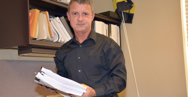 The National Cotton Councilrsquos Don Parker holds the stack of paperwork submitted by the NCC to EPA for the reregistration of one product