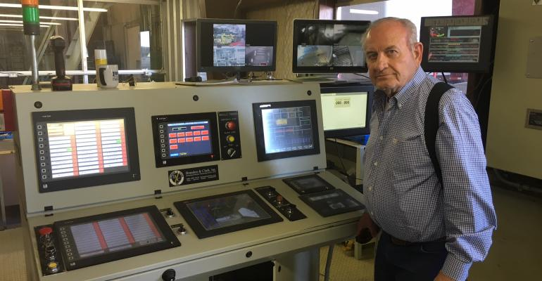 Jerry Harris King Mesa CEO at the controls of the machine that sends a DNA marker to the lint flue in the Lamesa cotton gin
