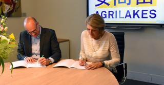 Two people signing an agreement at a table. It says Agrilakes in the background