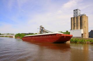 Grain barge sitting by grain silos in Mississippi River.