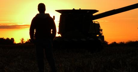 silhouette of farmer and combine