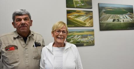 Tom and Judy McCarty standing infront of an aeriel image of the families dairy farms