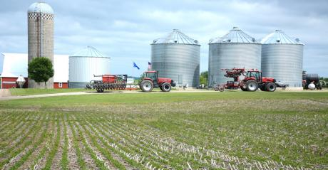 farmstead with tractors, grain bins, silo and cornfield