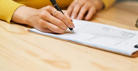 Closeup shot of an unrecognizable woman filling in paperwork on a clipboard at a table