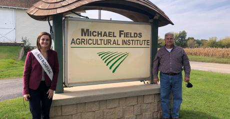 Julia Nunes with Perry Brown standing next to the Michael Fields Agricultural Institute Sign