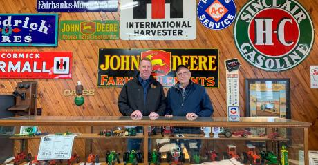 Father and son Doug and John Aylward standing in front of a collection of tractors in glass case